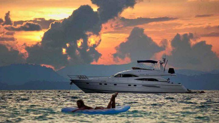 Девушка и яхта на закате в море