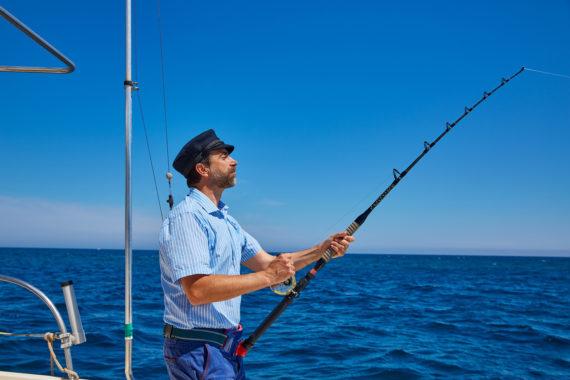 Рыбак на катере в море с удочкой